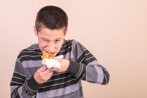 enfant mangeant de la pizza et un clin d'œil photo