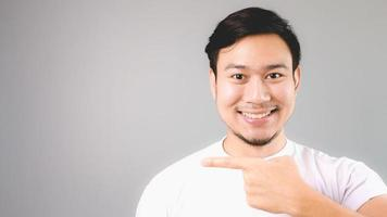 pointant vers le fond vide avec sourire visage heureux. photo
