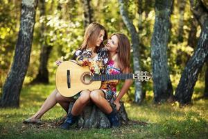 deux filles hippies avec guitare dans une forêt d'été photo