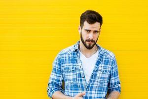 jeune bel homme avec un casque sur le mur jaune photo
