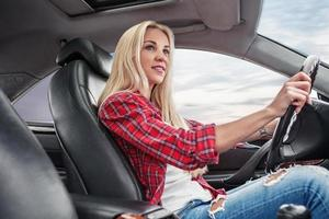 jeune blonde conduire une voiture photo