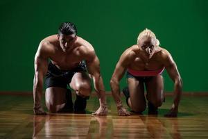 couple musclé fort à genoux sur le sol