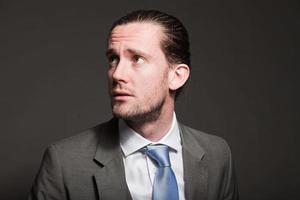 homme d'affaires cheveux longs portant costume gris. photo