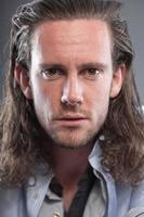 homme aux cheveux longs et visage expressif portant une chemise bleue. photo