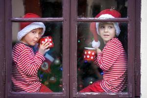 deux garçons mignons, frères, regardant par la fenêtre, attendant le père Noël photo