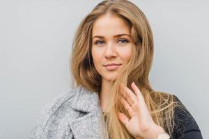 femme cheveux blonds marchant dans la rue et sourire