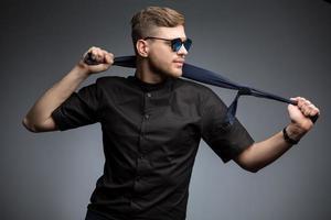 homme élégant en chemise noire et lunettes de soleil miroir photo
