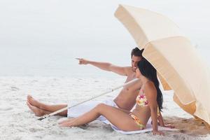 homme montrant quelque chose à sa petite amie sous un parasol photo