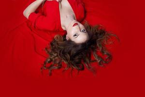 femme en robe se trouve sur un fond rouge photo