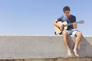 joueur de guitare pratiquant sur la jetée photo