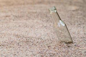 bouteille en verre vide sur la plage photo