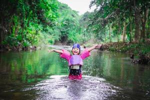 jeune fille asiatique jouant dans un ruisseau