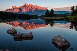rochers dans l'eau près de la chaîne de montagnes au coucher du soleil