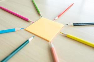 De nombreux crayons de couleur différents sur un bureau en bois