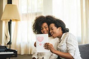 fille donnant à maman une carte de fête des mères photo