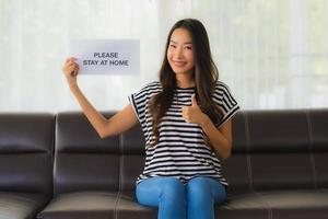 Woman holding up sign pour rester à la maison en donnant les pouces vers le haut photo