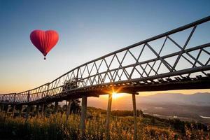 ballon à air chaud en forme de coeur survolant le coucher du soleil