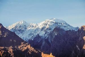 La lumière du soleil du matin brille sur la montagne enneigée