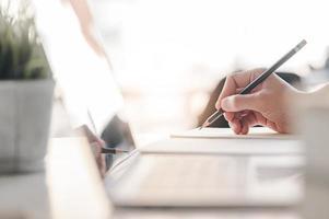 une main qui écrit sur un ordinateur portable avec un crayon