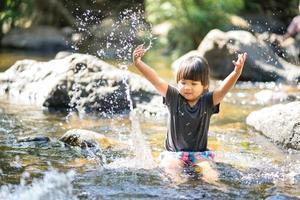jeune fille asiatique jouant dans le ruisseau