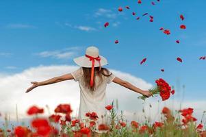 femme au chapeau blanc et robe se tient à bras ouverts