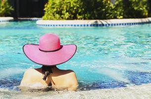 femme au chapeau rose se détendre dans la piscine