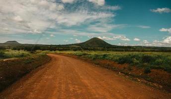 Chemin de terre à travers la colline sous un ciel nuageux photo