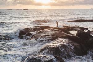 Personne debout sur une formation rocheuse brune photo