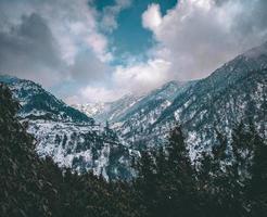 montagnes enneigées bleues sous un ciel nuageux