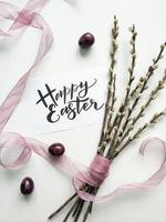 Bouquet de saule avec signe de Pâques sur une surface blanche photo