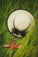 chapeau en osier dans les hautes herbes vertes photo