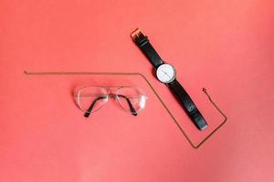 collier en or, lunettes et montre