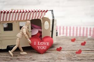mannequin jouet tenant un oreiller en forme de coeur photo