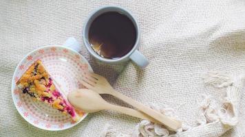 Gâteau au fromage aux myrtilles sur une assiette avec une tasse de thé