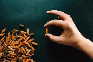 main tenant un morceau de macaroni avec d'autres macaronis photo