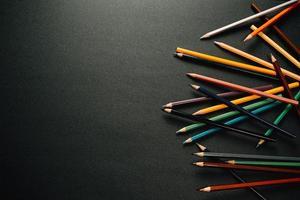 crayons colorés sur un côté du fond sombre
