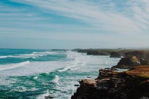 falaises rocheuses, eau et ciel nuageux