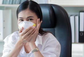 femme assise au bureau portant un masque