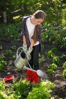 fille arrosage jardin avec arrosoir à chaude journée d'été photo