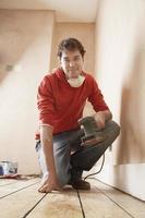 Homme tenant une ponceuse à genoux dans une pièce non rénovée photo