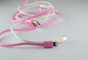 Câble usb rose et blanc sur fond gris photo