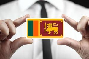 homme d & # 39; affaires détenant une carte de visite avec le drapeau du sri lanka photo