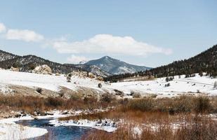 champ enneigé et ruisseau par montagne