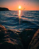 formations rocheuses brunes près d'un plan d'eau au coucher du soleil photo