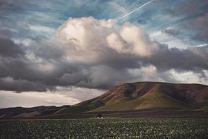 champ vert et montagne sous un ciel nuageux