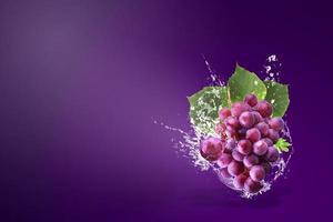 éclaboussures d'eau sur des raisins rouges frais photo