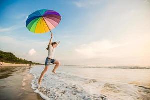 joyeuse jeune fille avec parapluie arc-en-ciel s'amusant sur le