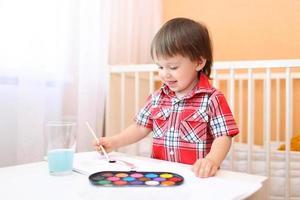 petit garçon de 22 mois avec pinceau et peintures photo