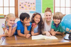 élèves mignons et enseignant souriant à la caméra en classe