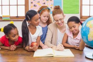 élèves mignons et enseignant souriant à la caméra en classe photo